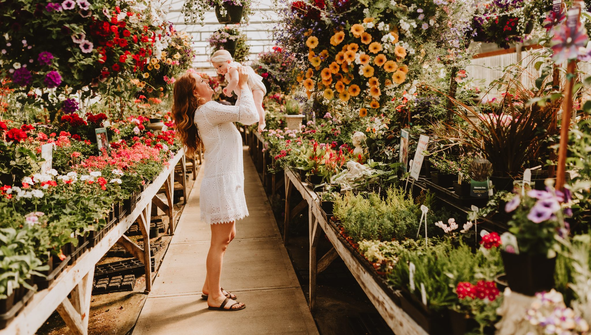 Mum holding up baby girl in front of flowers at garden centre during family photoshoot