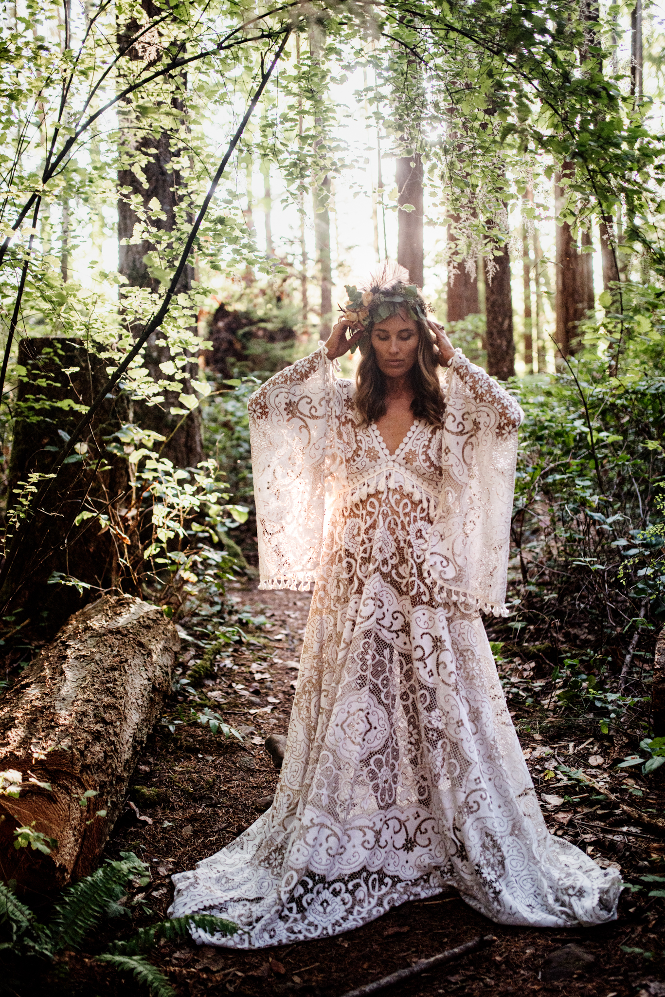 Woman in forest wearing flower crown and vintage lace reclamation design company gown for lifestyle photoshoot