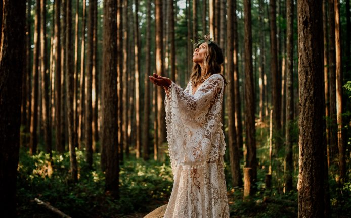 Woman in forest wearing reclamation design company dress