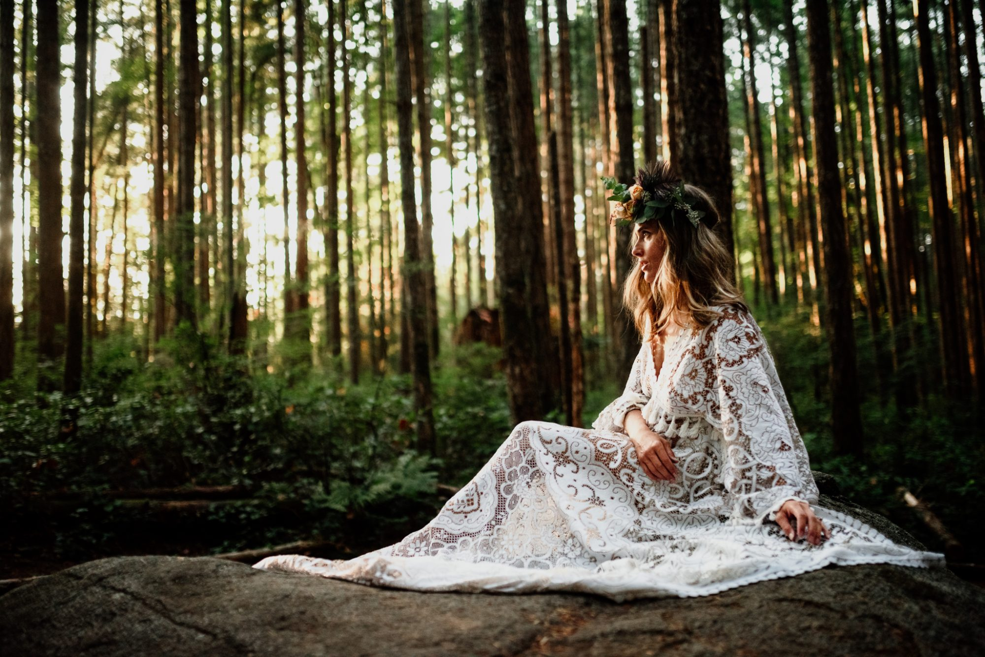 Woman in forest wearing vintage lace reclamation design company gown for lifestyle photoshoot