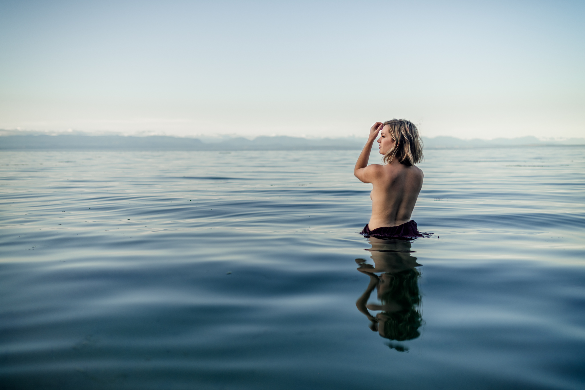 back of woman in the water at sea during lifestyle photography portrait shoot