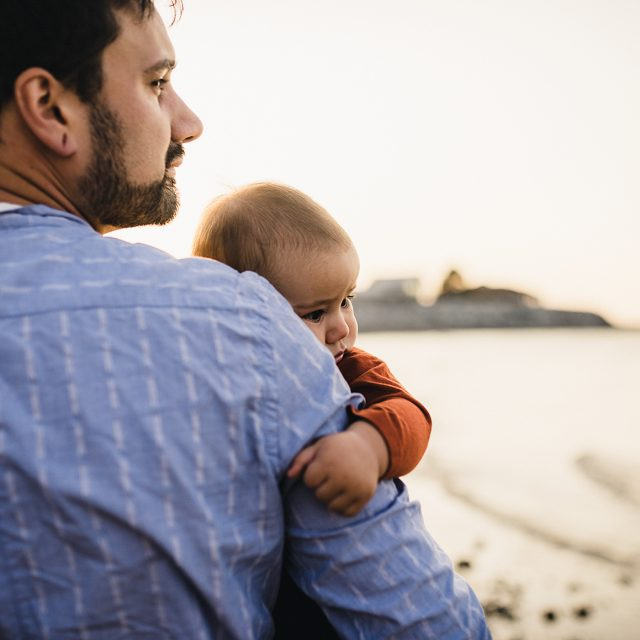 Dad and baby looking out to sea