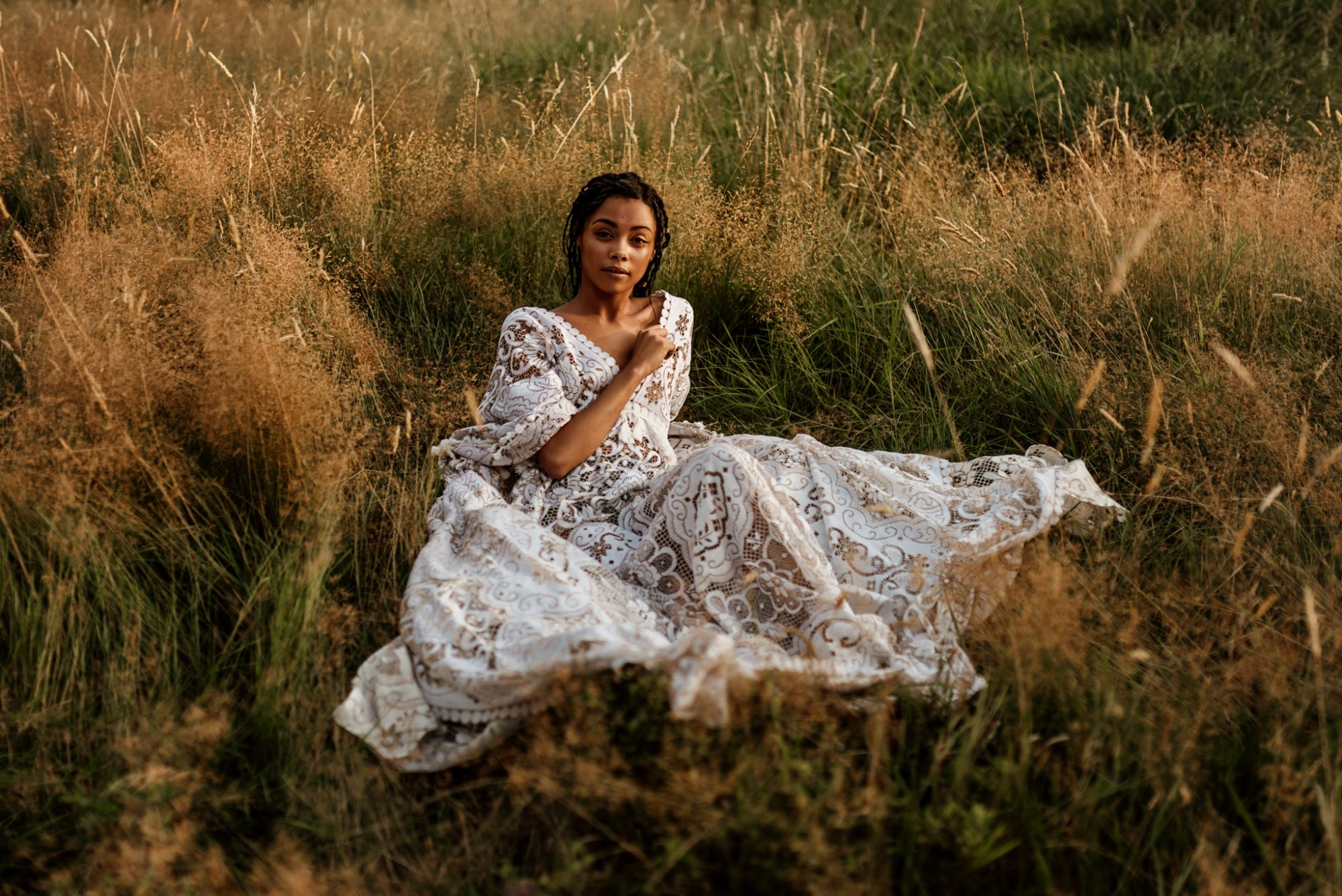 Woman in golden field wearing vintage lace reclamation design company gown for lifestyle photoshoot
