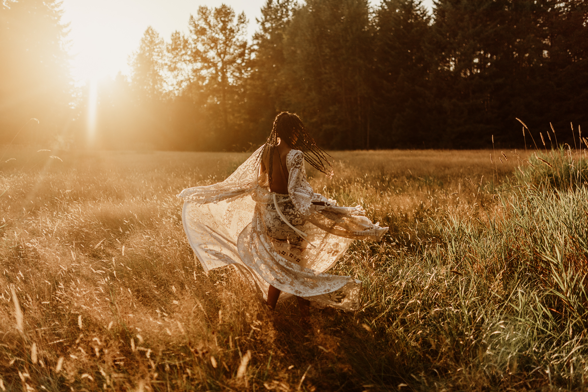 woman dancing in field wearing vintage lace reclamation design company gown for lifestyle photoshoot